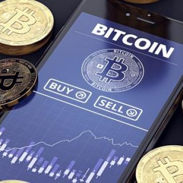 Złote monety bitcoin z telefonem